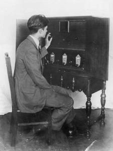 John Gelso, Chief Engineer of the Pilot Electric Mfg. Co. and designer of the Pilot Television Apparatus used in WRNY's television transmissions, adjusting the complete television receiver, and is observing a picture through the square opening in the cabinet.