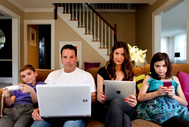Michael Combs, second from left, with his family using electronic devices.