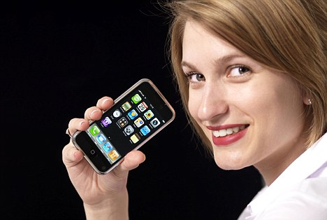 B17R2E Attractive young blond woman holding iPhone mobile phone.. Image shot 2008. Exact date unknown.