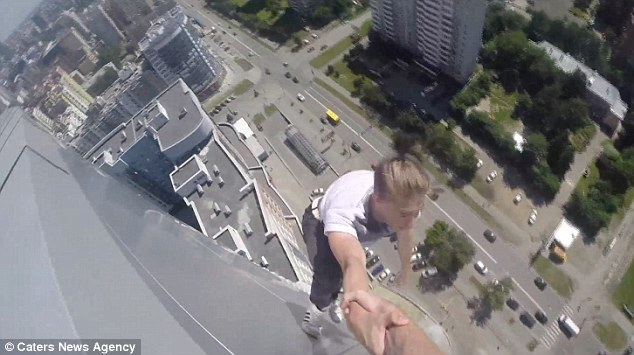https://au.news.yahoo.com/video/watch/29328809/russian-daredevil-hangs-from-40-storey-building/