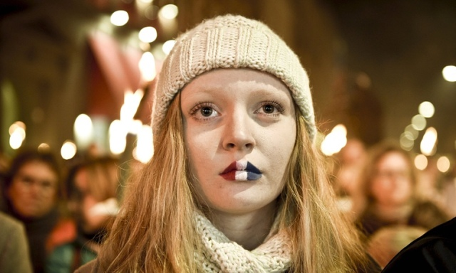 A woman with her lips painted in the French colours attends a commemoration event in front of the French Embassy in memory of victims of the Paris attacks, in Copenhagen, Denmark, November 15, 2015. Photograph: Scanpix Denmark/Reuters