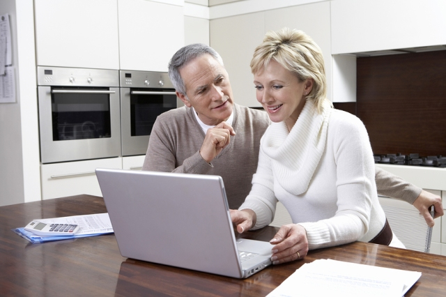 Happy middle aged couple calculating home finances on laptop at