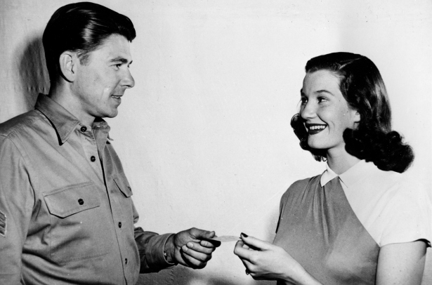 In 1947, Lois Maxwell, 20-year-old Canadian-born actress, receives her Screen Actors Guild member card from the new president of the guild, actor Ronald Reagan, in Hollywood, Calif. Maxwell, starred as Miss Moneypenny in 14 James Bond movies (AP Photo)